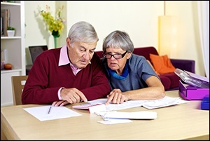Elderly couple writing checks